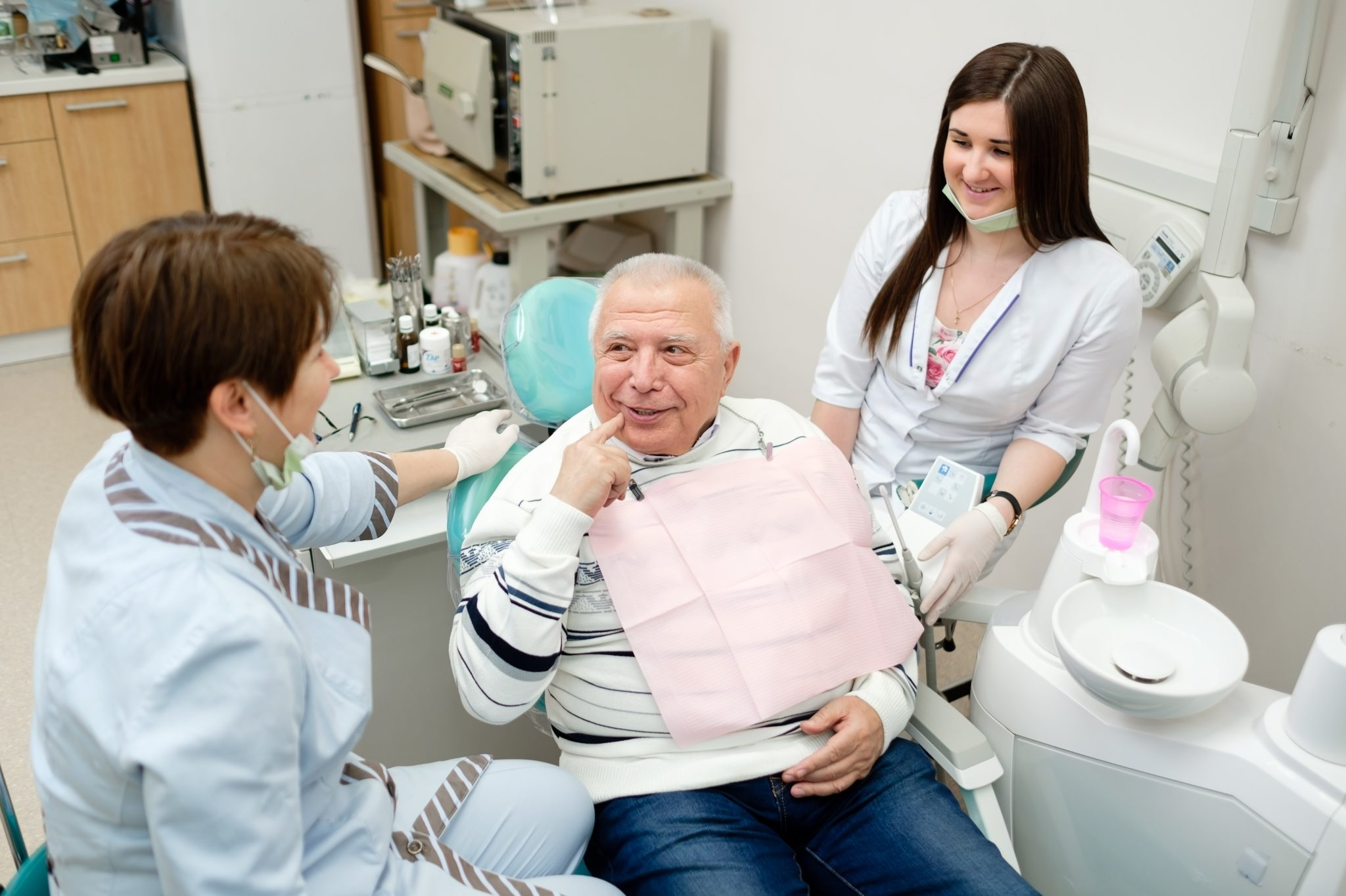 Dentist And Nurse Making Professional Teeth Checkup Male Senior Patient At The Dental Office. Dental Care For Older People. Dentistry, Medicine And Health Care Concept